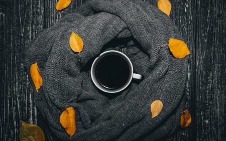 Bella tazza bianca con caffè. Quale essere in una sciarpa lavorata a maglia. ed è decorato con foglie gialle. Archivio Fotografico