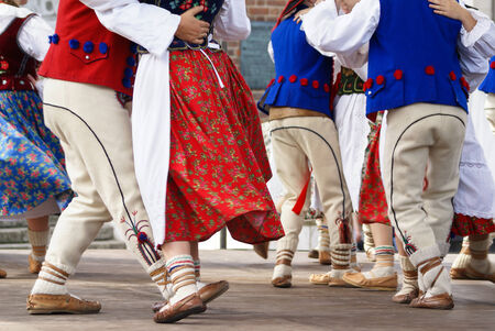 Horizontal colour image of female polish dancers in traditional folklore costumes on stage photo
