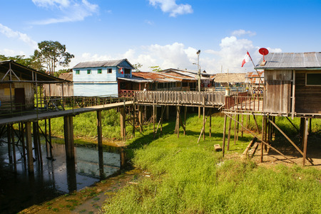 rise above: Houses on stilts rise above the polluted water in Islandia Peru