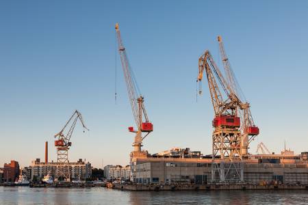 sea port cranes with blue cloudy sky in background and water in foreground in Helsinki port, Finland