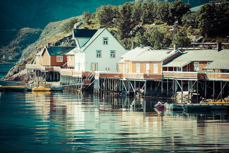 Typical Norwegian fishing village with traditional red rorbu huts, Reine, Lofoten Islands, Norway photo