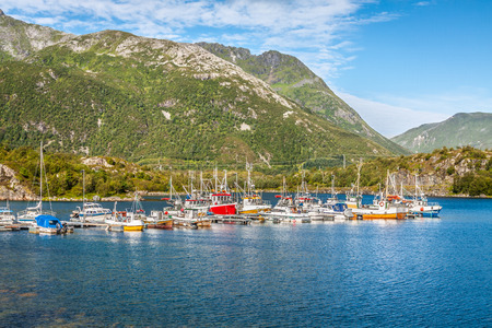 Red and white fishing boats stand moored in Norway village photo