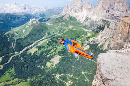 parachute jump: BASE jumper jumping off a big cliff in Dolomites,Italy, breathtaking Stock Photo