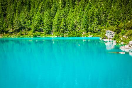 Turquoise Sorapis Lake with Pine Trees and Dolomite Mountains in the Back - Sorapis Circuit, Dolomites, Italy, Europe photo