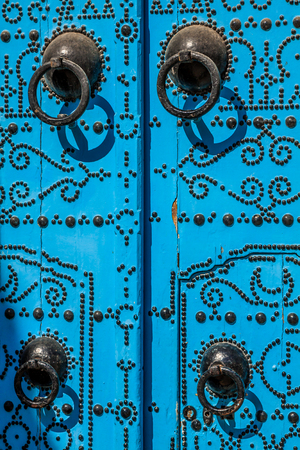 A blue door with black studs and stone ornament at doorway in Tunisia photo