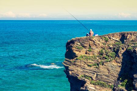 fisherman on the rocks,Ribadeo, Spain photo