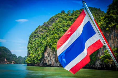 karst: Sailing to Phi Phi island, a famous travel destination in the Andaman sea in south Thailand. The flag is Thailand national flag.