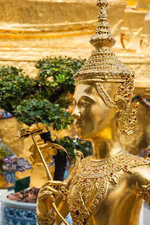 Golden Kinnari statue at Temple of Emerald Buddha (Wat Phra Kaew) in Grand Royal Palace. Bangkok, Thailand photo