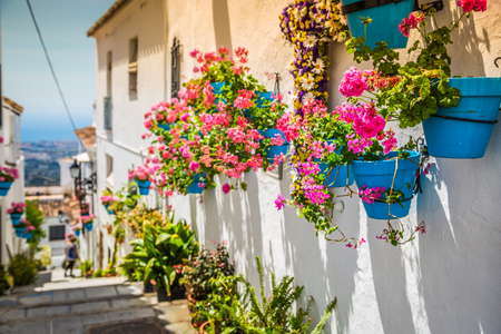 spanish houses: Picturesque street of Mijas with flower pots in facades. Andalusian white village. Costa del Sol. Southern Spain Stock Photo