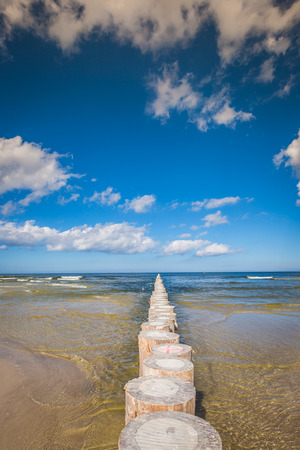 breakwaters: Wooden breakwaters on sandy Leba beach in late afternoon, Baltic Sea, Poland Stock Photo