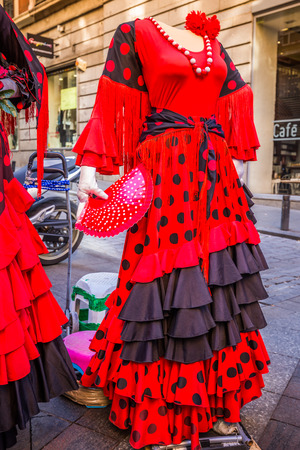 Beautiful traditional red flamenco dress hanged for display in a shop Spain Editorial