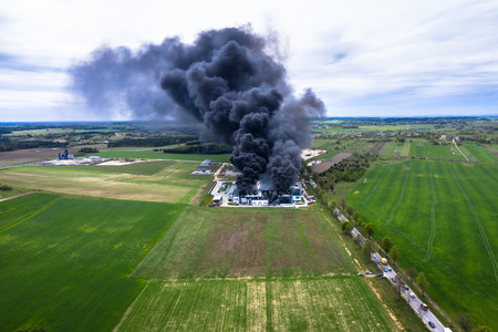 Top down view of smoke clouds from burnt warehouse building with burned roof, fire disaster accident in cargo logistics storehouse Redakční