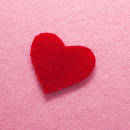 Felt red heart on pink background as a greeting card.