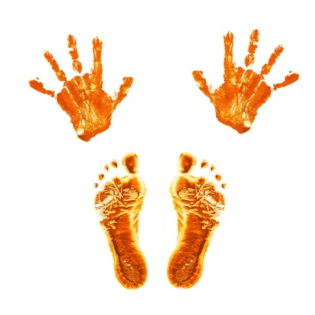 Orange prints of childrens painted hands and feet. Isolated on white background. photo