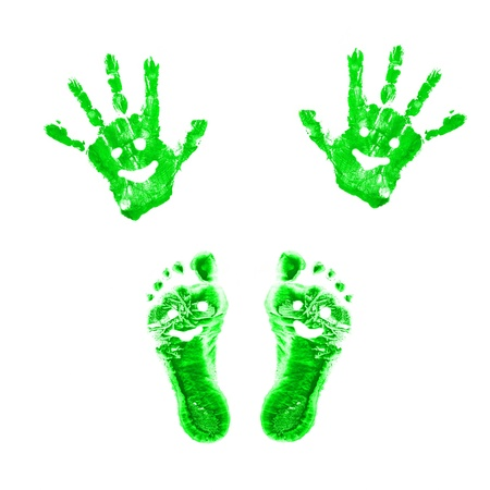 Green smiling prints of childrens painted hands and feet. Conceptual symbol of eco-friendly person. Isolated on white background. photo