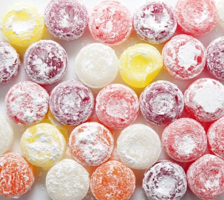 Sweet colorful candies lollipops in powdered sugar. Food background. Standard-Bild