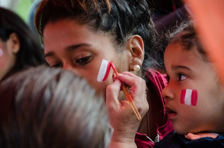 Lima, Peru - OCTOBER 10th 2017: Fanaticism in Peru (Peru vs. Colombia) Russia 2018. A fan painting his face with the colors of the Peruvian flag, preparing for the match
