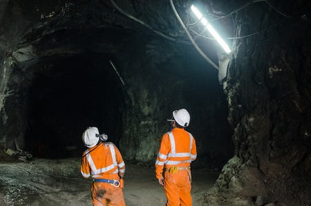 Two miners observing the cavern