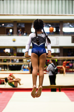 Athletic little girl gymnast performing exercises at the bar in the championship Stock Photo