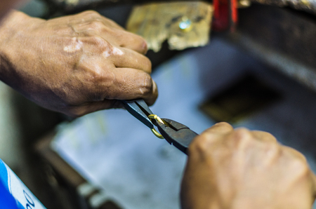 Hands of a jeweler working on a gold ring with a pliers Stock Photo