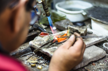 Master jeweler welding an ornament in a jewelry workshop. Image of hands and product close up.
