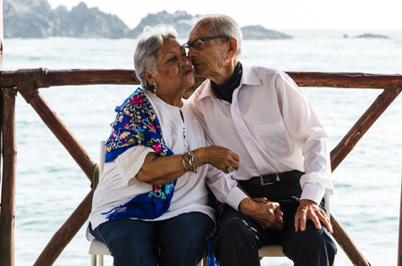Elderly couple sitting on chairs kissing with the beach background