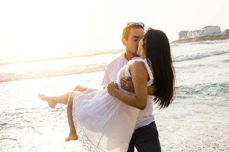 Young man carrying his girlfriend in his arms at the beach