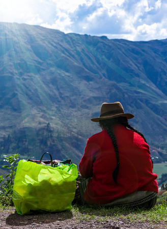 Woman in national Peruvian multicolored clothes and in tall brown felt hat sits backside near the cliff and observe at the valley in the Andes mountains.