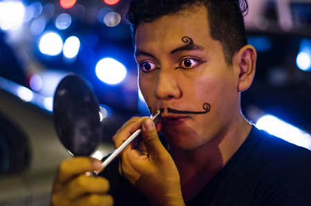 Portrait of a young clown putting on mustaches with makeup.
