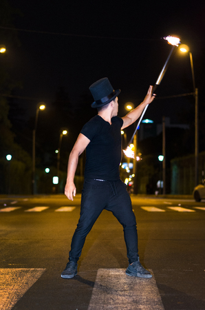 A street artist who makes a show in Lima - Peru, juggling a stick with fire at traffic lights stops, in front of stopped cars