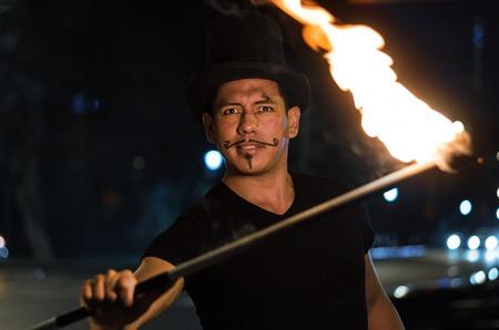 Un artiste de rue qui fait un spectacle à Lima - Pérou, jonglant avec un bâton avec le feu aux feux de circulation, devant des voitures arrêtées Banque d'images