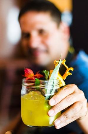 Young man smiling holding orange juice, closeup shot Stok Fotoğraf - 123216930