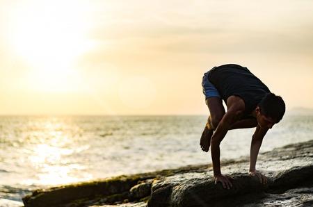 Summer yoga session on a beautiful golden beach of Lima in Peru yoga tour, Bakasana Crow Crane pose