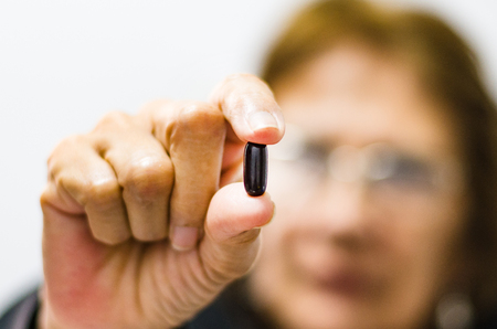 Adult woman showing a pill in the foreground, seniors health concept . Stockfoto