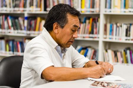 Älterer Mann, der in einer Bibliothek sitzt und in einen Notizblock schreibt.