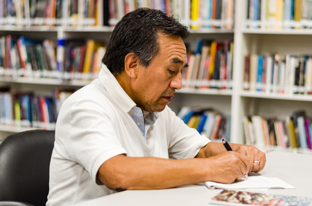 Senior man sitting in a library writing in a notepad .