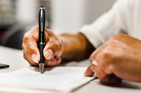Close shot of a human hand writing something on the paper on the foreground . Reklamní fotografie