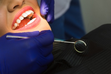 Professional dentist. Smiling pretty woman is having her teeth examined by the dentist in clinic.