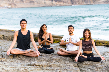 fitness, sport, yoga and healthy lifestyle concept - group of people meditating in lotus pose over exotic tropical beach background Stok Fotoğraf