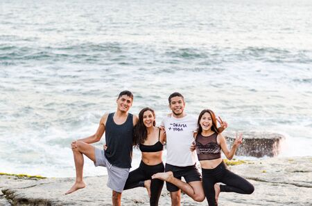Group of people doing yoga exercises and smiling on the beach Фото со стока - 134680580