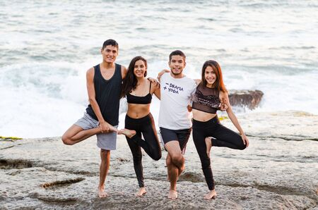 Group of people doing yoga exercises and smiling on the beach