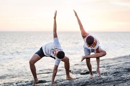 Two friends practicing Yoga on the edge of the ocean at sunset, Yoga or meditation concept Фото со стока - 134680595