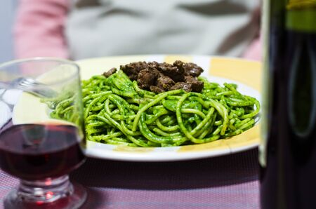 Peruvian spaghetti with meat and cream of green basil viewed from above on a white plate, homemade food accompanied with wine Stok Fotoğraf