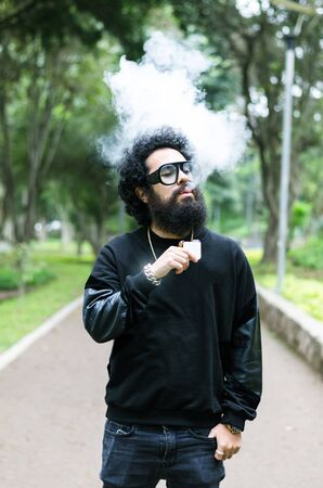 Vape. Young brutal man with large beard and fashionable haircut in sunglasses smoking an electronic cigarette in the city park. Steam cloud. Lifestyle.