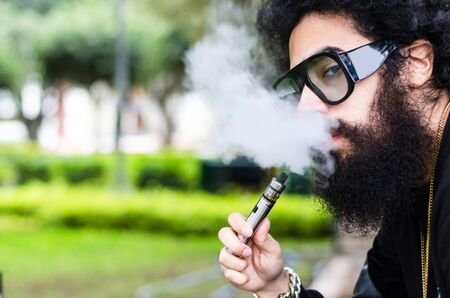 Bearded man smokes vape close up. Electronic cigarette concept. Man with long beard and clouds of smoke looks relaxed. Man with beard and mustache on calm face, branches on background, defocused. Stok Fotoğraf