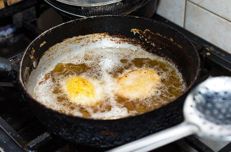 Fried potatoes in a frying pan on stove. Homemade cuisine. Potatoes is frying on stove.