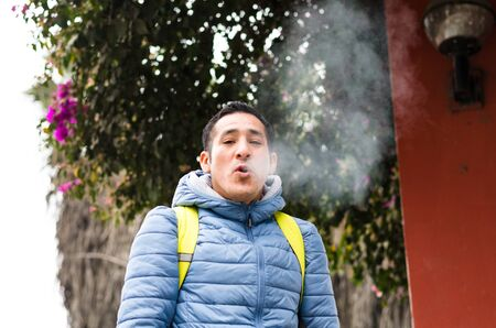 A man with a backpack smoking and smoke coming out of his mouth