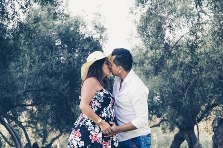 A beautiful outdoor pregnant couple portrait in summer nature Stock Photo