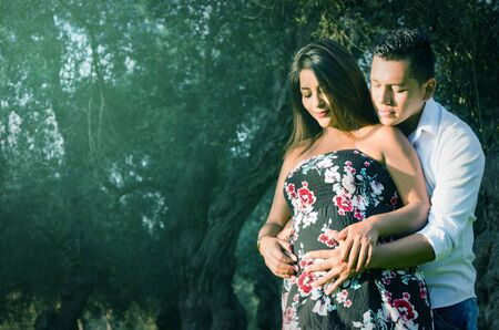 Happy and young pregnant couple hugging in nature, outdoors, waiting for a baby Zdjęcie Seryjne - 132098260