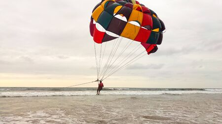 Parasailing extreme sports on the beach at sunset